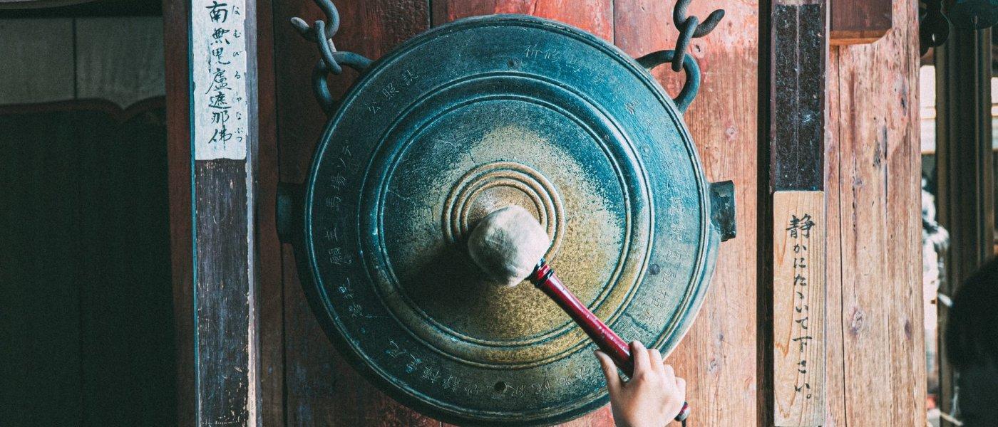 Nara, Japan, Boy bangs a gong.